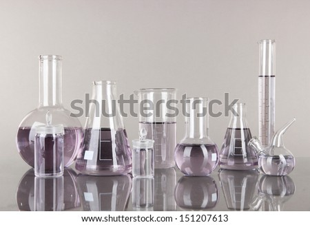 Test-tubes with light purple liquid on gray background - stock photo