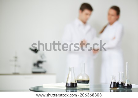 Test-tubes with liquid oil on background of two scientists working in laboratory - stock photo