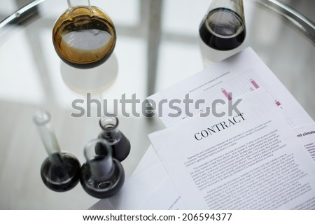 Test-tubes with liquid oil over contract in laboratory - stock photo
