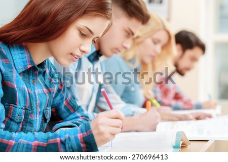 Testing. Closeup of young students sitting in a row and having test in their test-books - stock photo