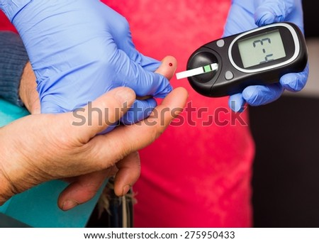 Testing elderly man's blood sugar level. - stock photo