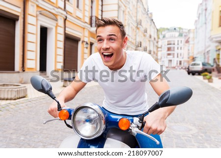 Testing his new scooter. Happy young man riding scooter along the street and keeping mouth open - stock photo