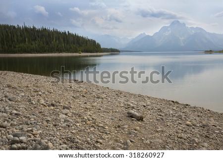 Teton mountains over Jackson Lake, with clouds, pine forest peninsula, and stones on the beach, Teton National Park, Wyoming. - stock photo