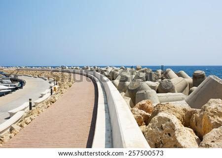Tetrapods concrete breakwaters in sea marina port. Promenade road near yachts. - stock photo