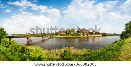 Teutonic Castle in Malbork (Marienburg) in Pomerania, Poland, Europe. UNESCO world heritage site. Blue sky with clouds in background and Nogat river in foreground. - stock photo