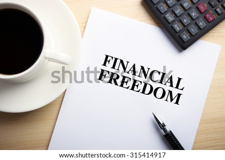Text Financial Freedom is on the white paper with coffee, calculator and ball pen aside. - stock photo
