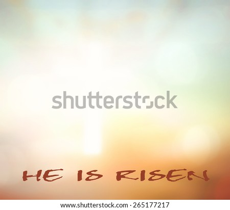 """Text for """"He Is Risen"""" over blurred the white cross on sunset background. - stock photo"""