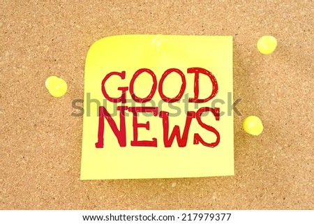 Text good news written by hand font on colored sticky note pinned on cork board - stock photo
