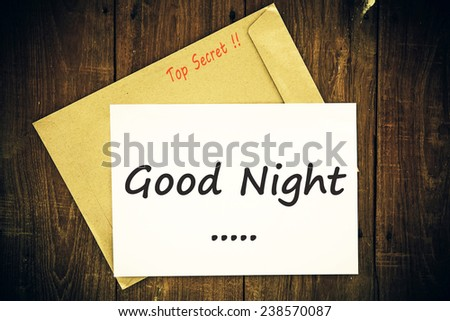 text good night on the short note vintage paper with tape on wood background  - stock photo