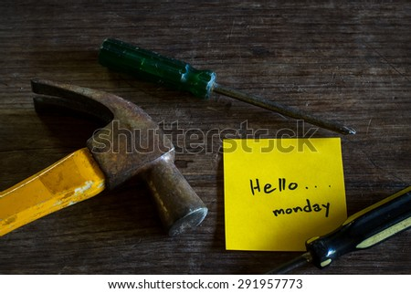 "Text ""Hello Monday"" on yellow short note paper with old tools laying on natural wood desk, still life image dark tone. - stock photo"