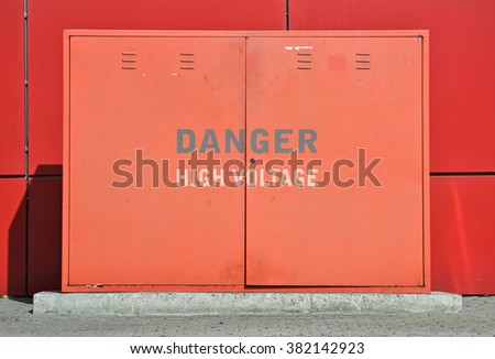 Text High Voltage written on a red street transformer - stock photo