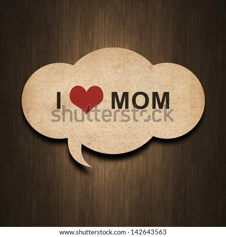 text i love mom on speech bubble paper on wood background - stock photo