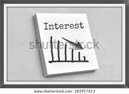 Text interest on the graph goes down on the short note texture background - stock photo