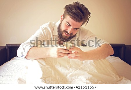 Text message early morning from bed - stock photo