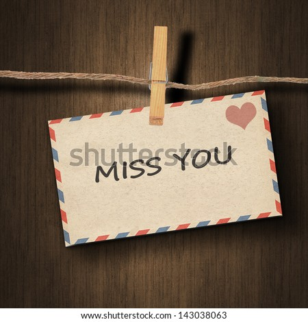 text miss you on the old envelope and clothes peg wood background - stock photo
