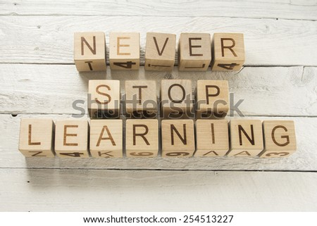 Text Never Stop Learning on a wooden background - stock photo