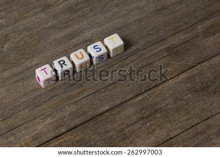 text of TRUST on a wooden background - stock photo