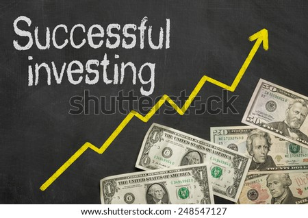 Text on blackboard with money - Successful investing - stock photo