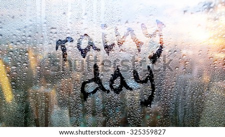 """Text """"rainy day"""" written on the wet window in the big city - stock photo"""