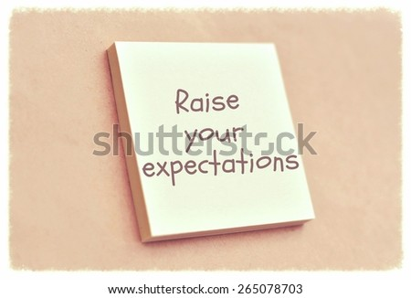 Text raise your expectations on the short note texture background - stock photo