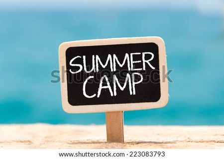 Text Summer camp written with chalk on chalkboard. ext Summer camp written with chalk on chalkboard, on sandy beach side  - stock photo