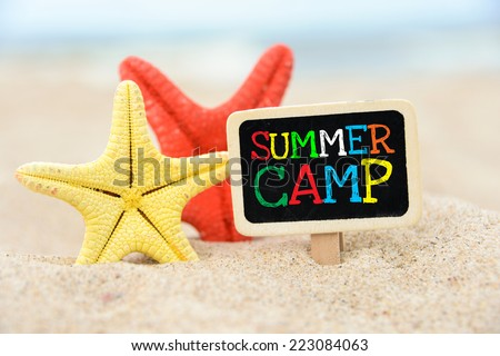 Text Summer camp written with chalk on chalkboard. Text Summer camp written with chalk on chalkboard, on sandy beach side with two sea stars  - stock photo