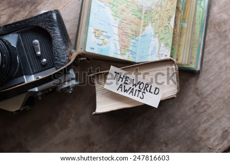 """text """"The World Awaits"""" and book, travel, tour, tourism concept - stock photo"""