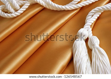 Textile background image of gold satin fabric with drapery cords (or graduation honor cords) - stock photo