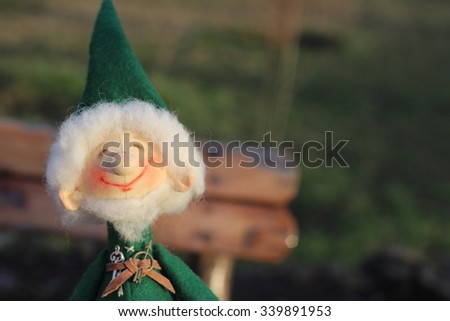 Textile doll gnome in a green jacket and a flashlight - stock photo