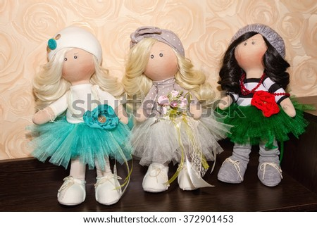 Textile dolls handmade on a stand wooden shelf Cabinet - stock photo