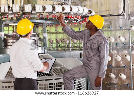 textile factory manager and worker checking yarn on weaving machine - stock photo