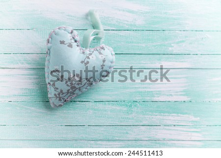 Textile heart  on aqua wooden background. Valentine day background. Selective focus. - stock photo