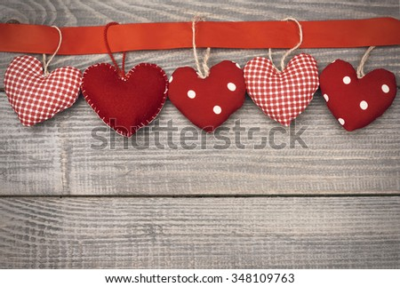 Textile hearts hung on red ribbon - stock photo