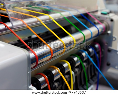 Textile machine with rainbow colors threads - stock photo