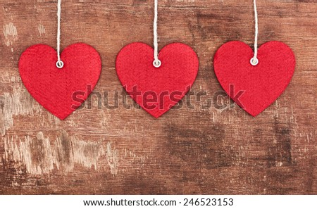Textile pendent hearts on old shabby wooden background - stock photo