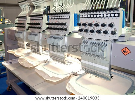 Textile - Professional and industrial embroidery machine. Machine embroidery is an embroidery process whereby a sewing machine or embroidery machine is used to create patterns on textiles. - stock photo