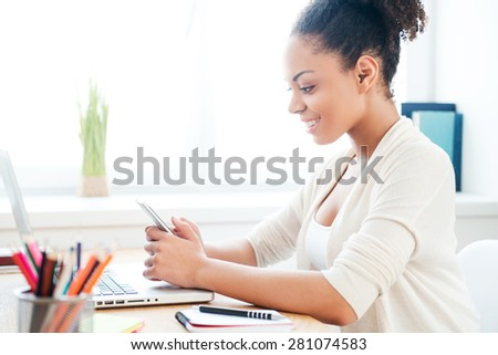 Texting to colleague. Side view of beautiful young African woman holding mobile phone and smiling while sitting at her working place in office - stock photo