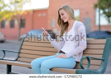 Texting. Woman sitting on a bench outside while using a smartphone. - stock photo