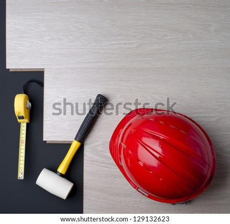 texture laminate, tape measure and a hammer with a red helmet - stock photo
