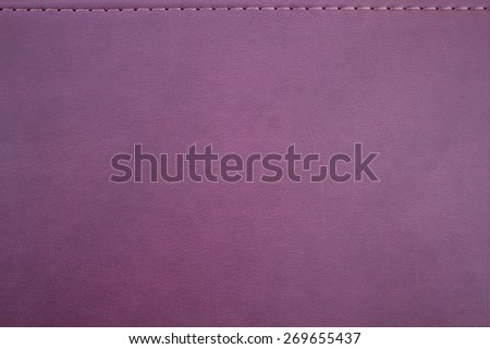 Texture of an imitation leather of crimson color with a seam - stock photo