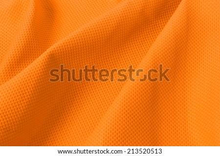 texture of bright, acid orange cloth with pleat - stock photo