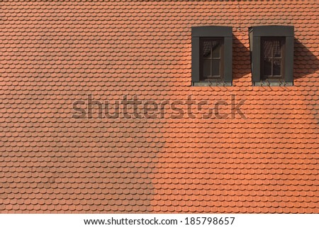 Texture of brown and red roof tiles with windows - stock photo