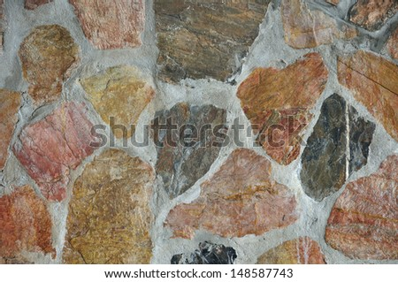 Texture of colorful stone in exposed concrete wall. - stock photo