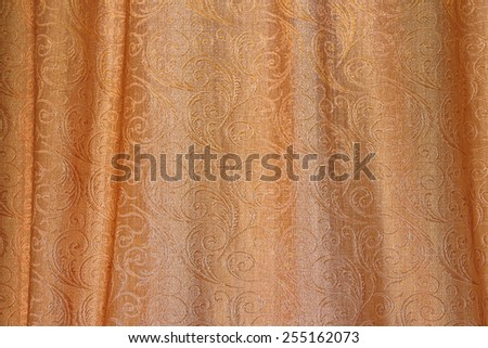 Texture of gold fabric with pleats and abstract ornaments - stock photo