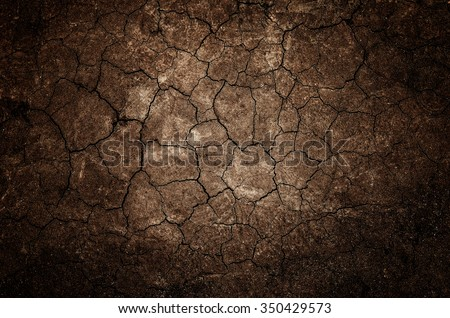 Texture of land dried up by drought, the ground cracks background with grunge and vignette tone - stock photo