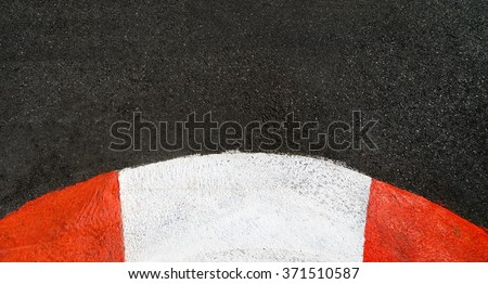Texture of motor race asphalt and curved red white curb. Close up on Monaco Montecarlo Grand Prix street circuit - stock photo
