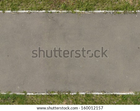 Texture of new, asphalt road in grey tone with grass at edges. - stock photo