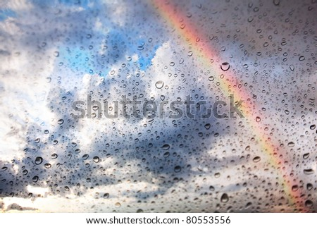 Texture of Rainbow, dramatic sky and water drops on the glass - stock photo