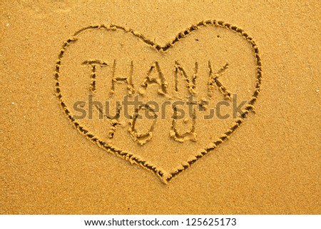 Texture of sand, the inscription inside the heart of Thank You. - stock photo