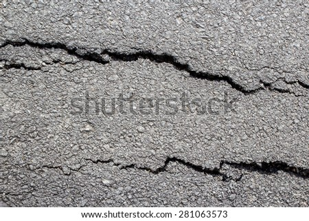 Texture of tarmac road with cracks. The road has cracks. - stock photo